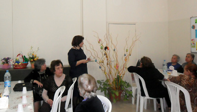 Rouzanna Salkhanian speaking about the spiritual significance of Easter during the elderly gathering.